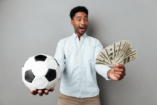 hombre con dinero en una mano y un balon en otra mano